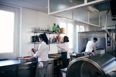 Female and male chefs working in commercial kitchen - MASF08664