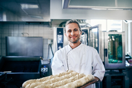 Portrait of confident chef baking breads in commercial kitchen - MASF08667