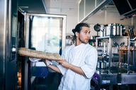Male chef putting bread in oven while looking away at commercial kitchen - MASF08670