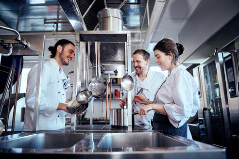 Smiling male and female chefs cooking food in commercial kitchen - MASF08673