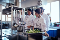 Chef team looking at colleague cooking food in commercial kitchen - MASF08676