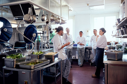 Male chef holding digital tablet while discussing with colleagues in commercial kitchen - MASF08679