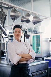 Portrait of mid adult female chef standing arms crossed in commercial kitchen - MASF08688