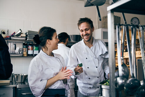 Male chef holding broccoli while talking with female colleague at kitchen - MASF08694