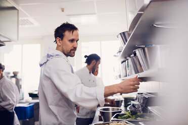 Young male chef reading order ticket in commercial kitchen - MASF08697