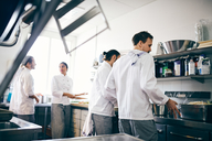 Chefs preparing food at counter in commercial kitchen - MASF08700