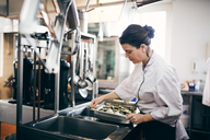 Mid adult female chef preparing food in commercial kitchen - MASF08703