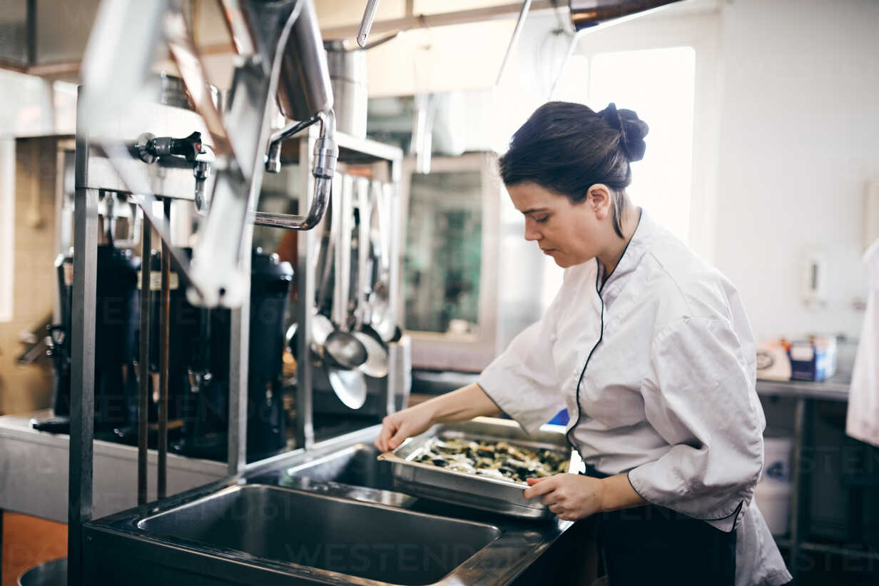 Mid adult female chef preparing food in commercial kitchen - MASF08703 - Maskot ./Westend61