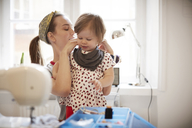 Female tailor tying scarf on daughter's neck while sitting at home - MASF08721