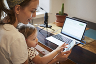 Podcaster showing mobile phone to daughter while using laptop at home - MASF08733