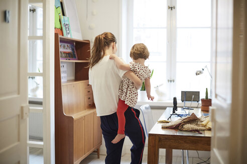 Female influencer carrying daughter while standing by table at home - MASF08739