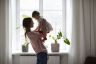 Side view of fashion designer carrying daughter while standing by window at home - MASF08745