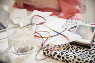 Close up of multi colored headphones and financial bills with smart phone on table - MASF08763