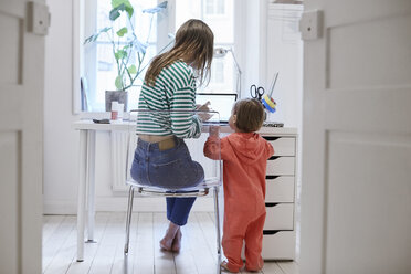 Rear view of girl standing by mother using laptop at table - MASF08775