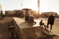 Friends hanging out at skateboard park in city during sunny day - MASF08808