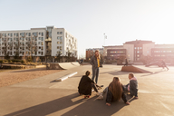 Teenage girl standing while talking to friends sitting at skateboard park in city - MASF08817