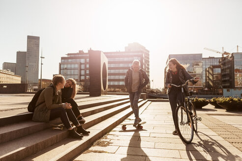 Teenage girl riding bicycle and boy skateboarding while friends sitting on steps in city - MASF08826