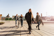 Teenagers walking on footpath against clear sky in city - MASF08832