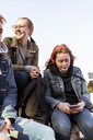 Teenage girl using mobile phone while sitting with friends against clear sky - MASF08841