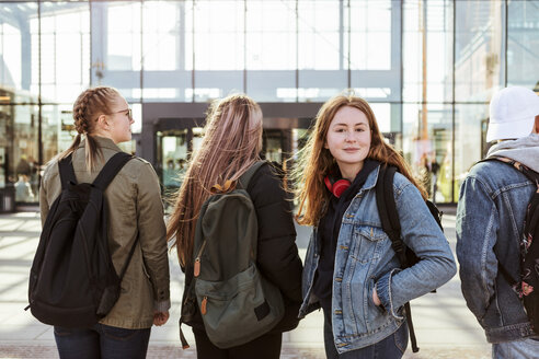 Portrait of teenage girl with friends against railroad station in city - MASF08847