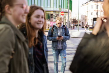 Teenage boy using mobile phone with friends standing in foreground at city - MASF08850