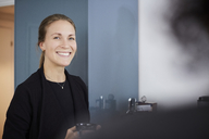 Portrait of smiling businesswoman holding coffee cup at office - MASF08859