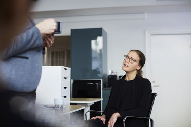 Female coworker discussing with businesswoman at office - MASF08874