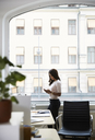 Side view of mature businesswoman using mobile phone while standing by window at office - MASF08883