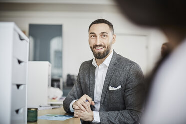 Smiling businessman looking at coworker while sitting in office - MASF08898