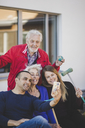 Cheerful multi-generation family taking selfie outside nursing home - MASF08907