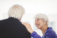 Side view of senior woman talking with man in nursing home - MASF08919