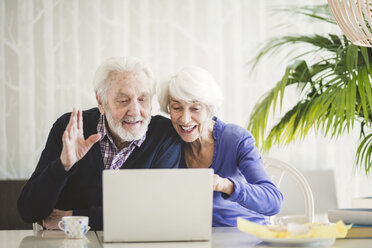Cheerful senior couple video calling through laptop at table in nursing home - MASF08922