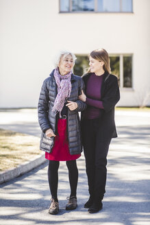 Full length of granddaughter talking while walking with grandmother on road outside nursing home - MASF08928