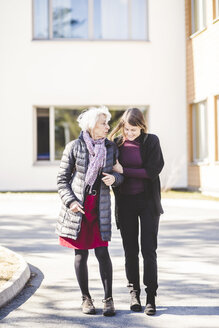 Full length of granddaughter walking with grandmother on road outside nursing home - MASF08931