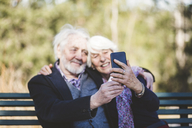 Smiling senior couple taking selfie while sitting on bench - MASF08934