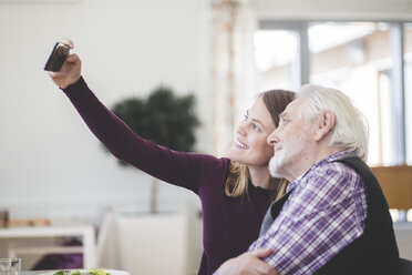 Young woman taking selfie with grandfather while sitting in nursing home - MASF08943