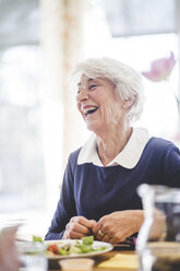 Cheerful senior woman having lunch at table in nursing home - MASF08949