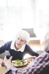 Senior man showing mobile phone to woman while having lunch at table in nursing home - MASF08955