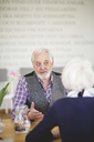 Senior man talking with woman while sitting at table in nursing home - MASF08961