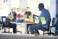 Adhesive notes stuck on glass while business professionals working in background - MASF08982