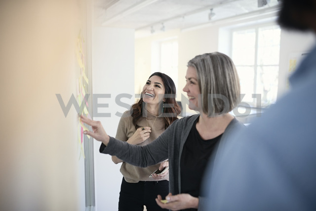 Mature female engineers smiling while reading adhesive notes stuck on glass in office - MASF08988