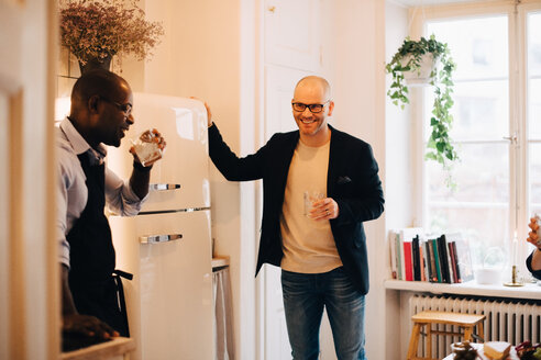 Smiling friends drinking water while standing by refrigerator in kitchen - MASF09021