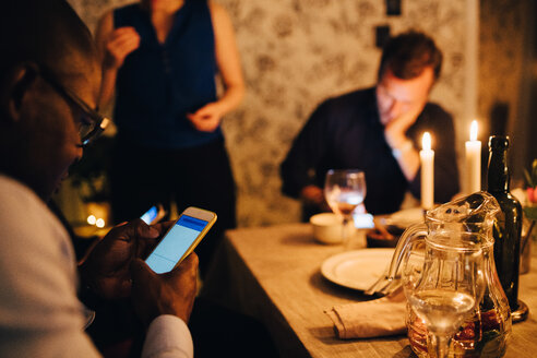 Mature man using mobile phone while having dinner with friends at party - MASF09027