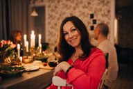 Portrait of smiling woman sitting with friends at dinner party - MASF09030