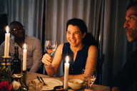 Happy woman enjoying dinner party with friends at home - MASF09033