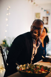 Happy male friend looking away while sitting at dining table in dinner party - MASF09042