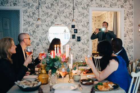 Man photographing mature friends at dinner party - MASF09051