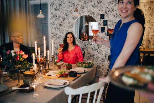 Woman enjoying drinks with friends at dining table in party - MASF09054