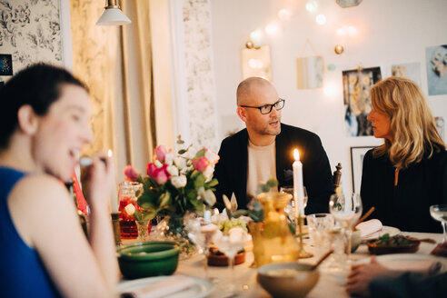 Mature friends talking while enjoying food at dinner party - MASF09066