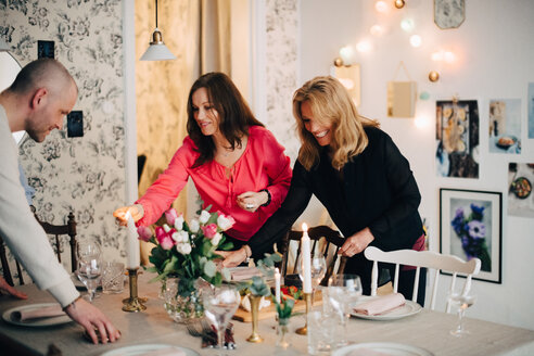 Mature male and female friends decorating dining table for party at home - MASF09069